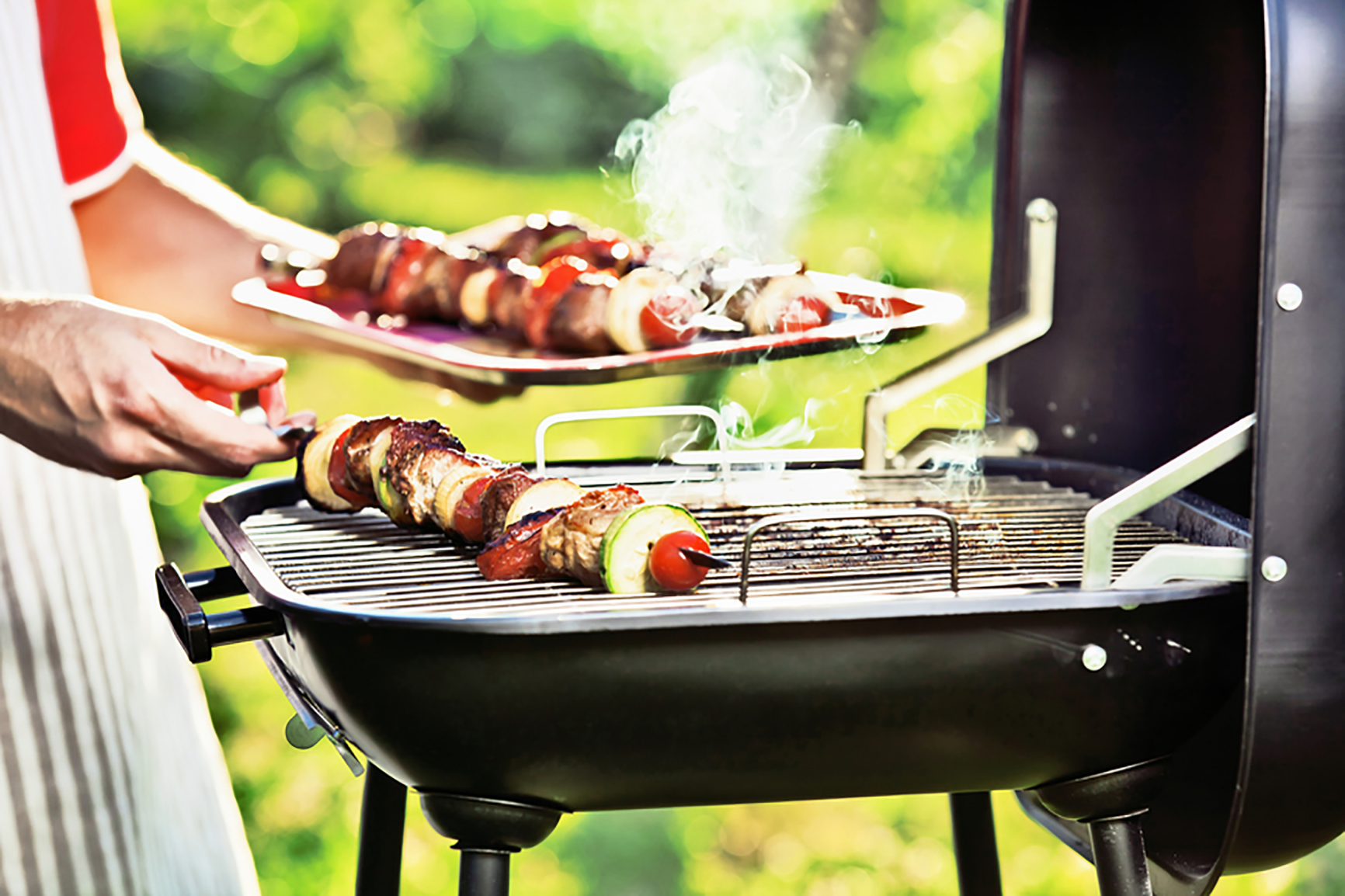 small barbecue grill with some grilled meat on sticks.